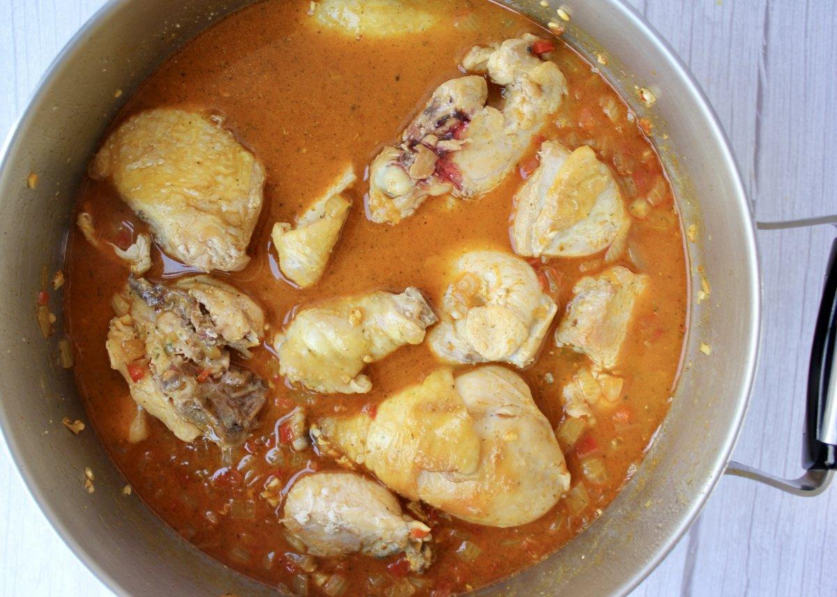 Adición del caldo de pollo y los trozos de pollo dorados para hacer el arroz con pollo