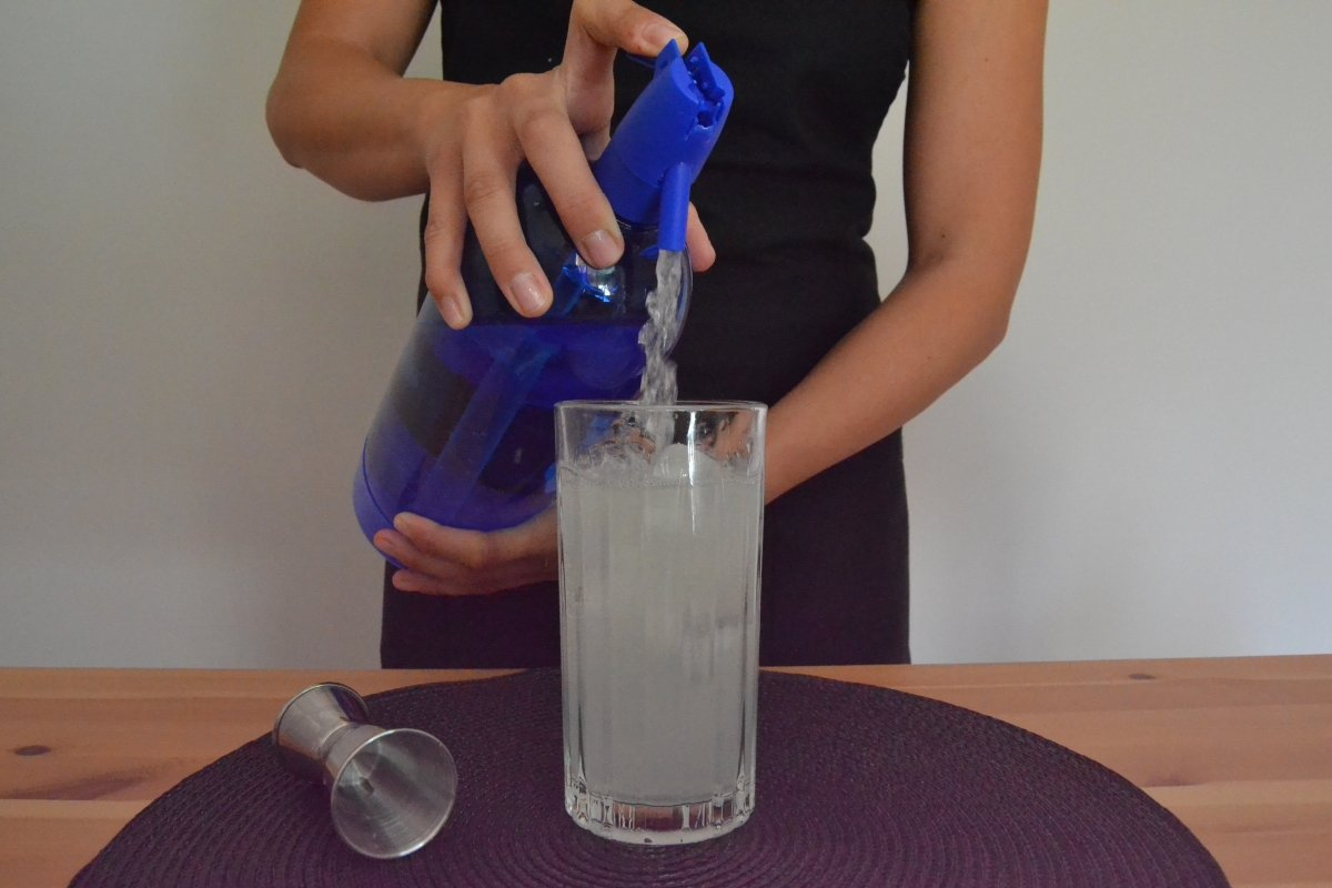 Agregamos soda hasta completar el vaso del cóctel Gin Fizz