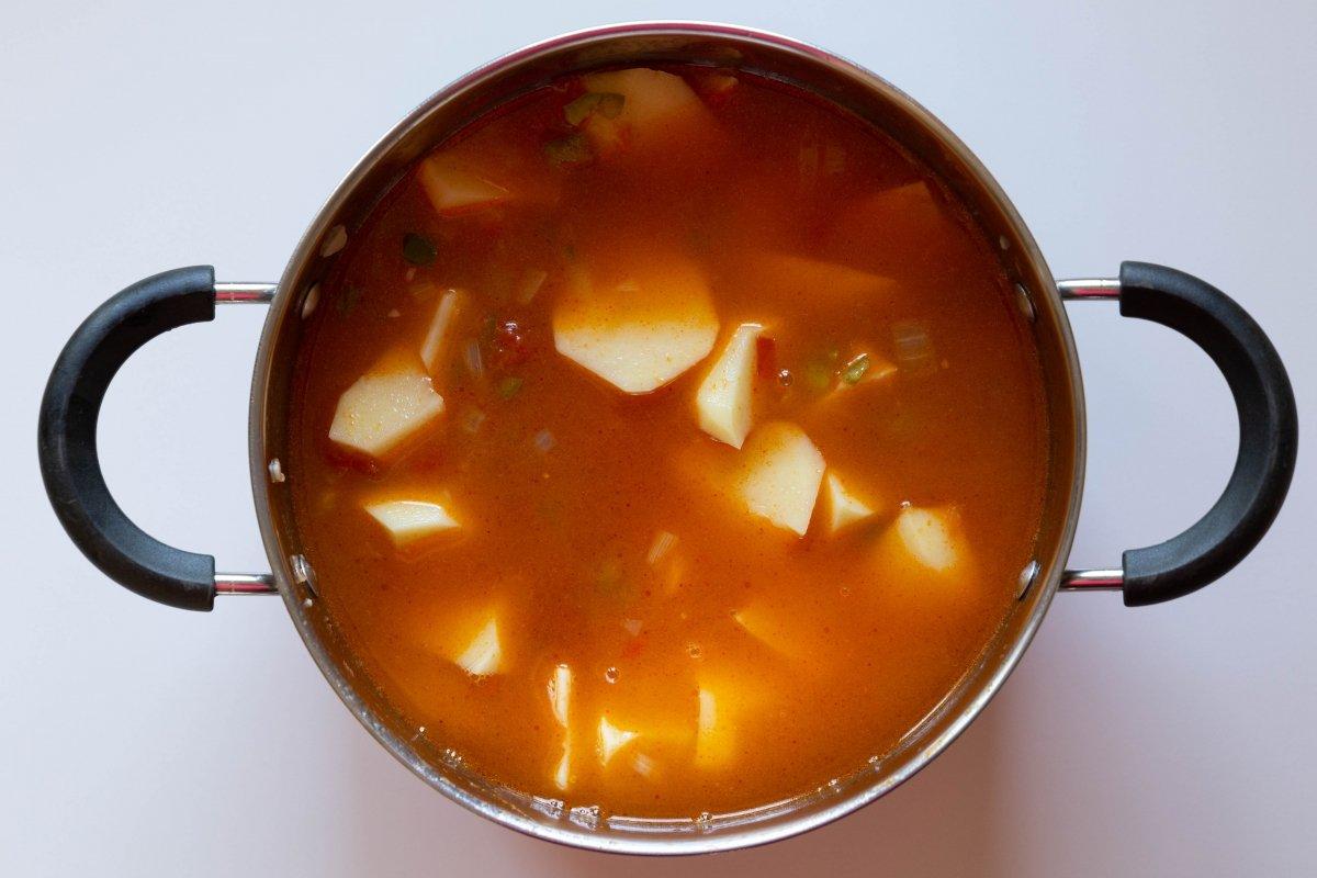 Agregar las patatas y cubrir con caldo