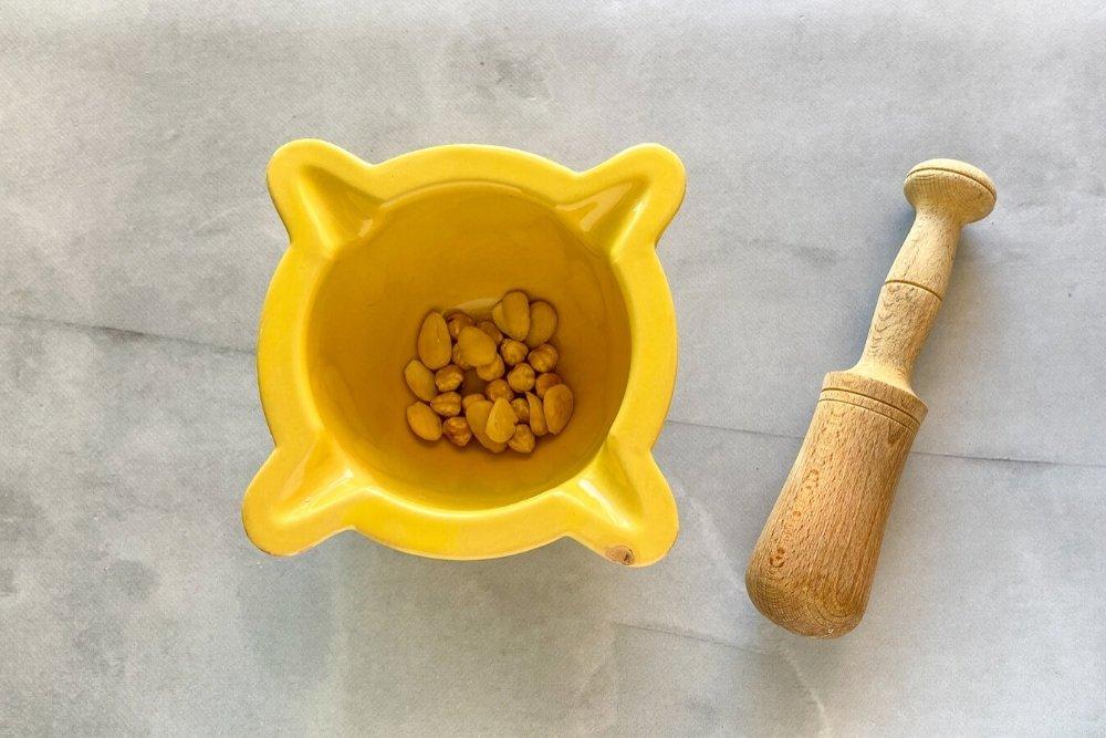 Almendras y avellanas en el mortero para elaborar ensalada xató