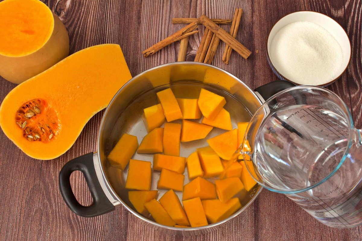 Añadiendo agua a la olla de la mermelada de calabaza