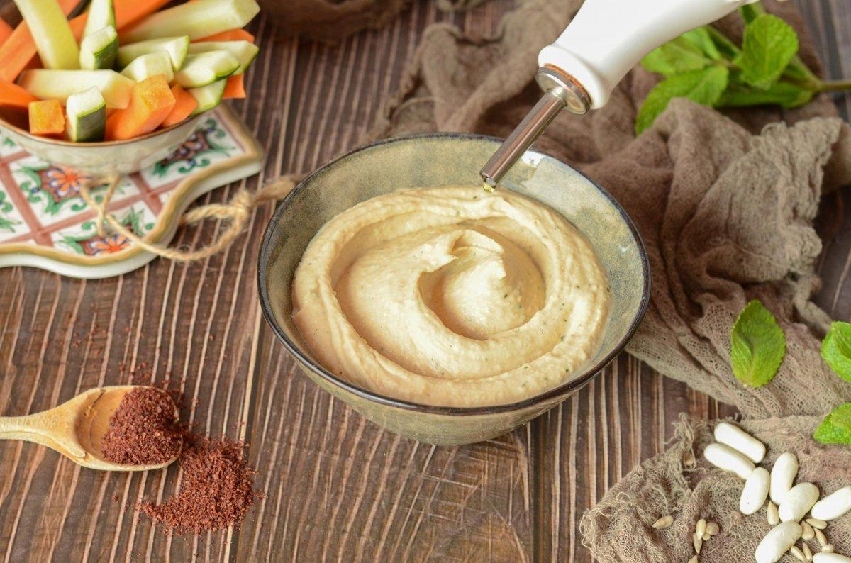 Añadiendo AOVE al humus de alubias blancas