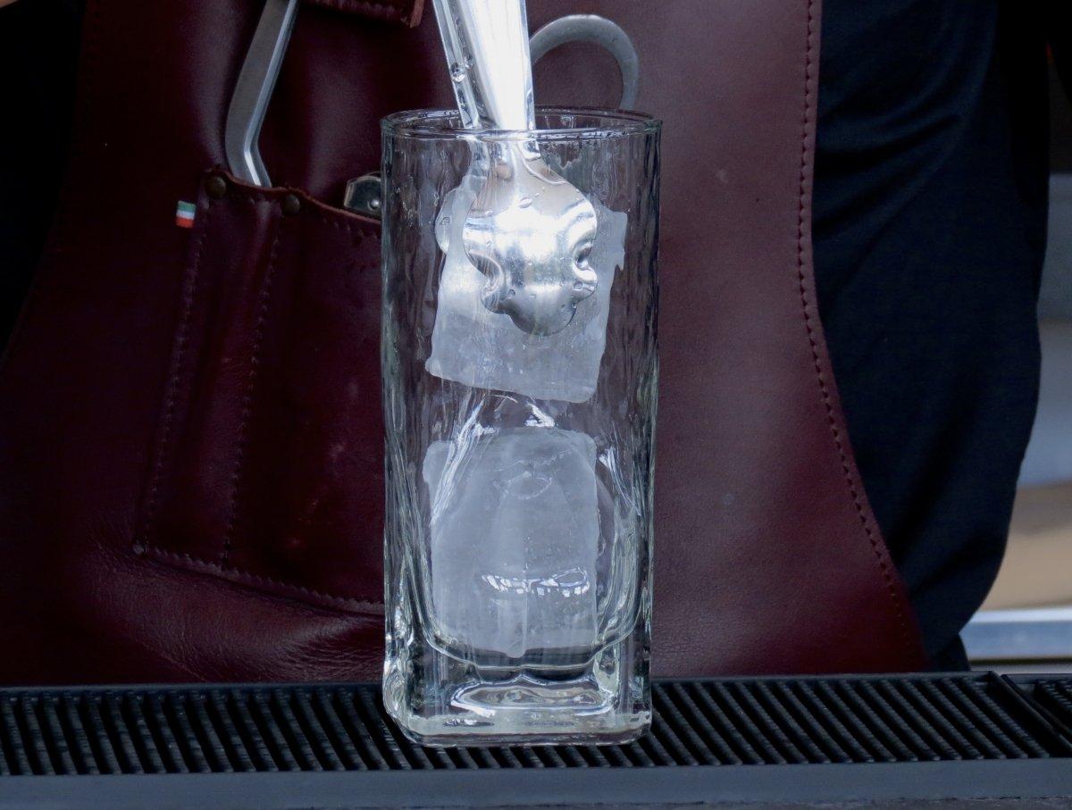 Añadiendo hielo en el vaso highball