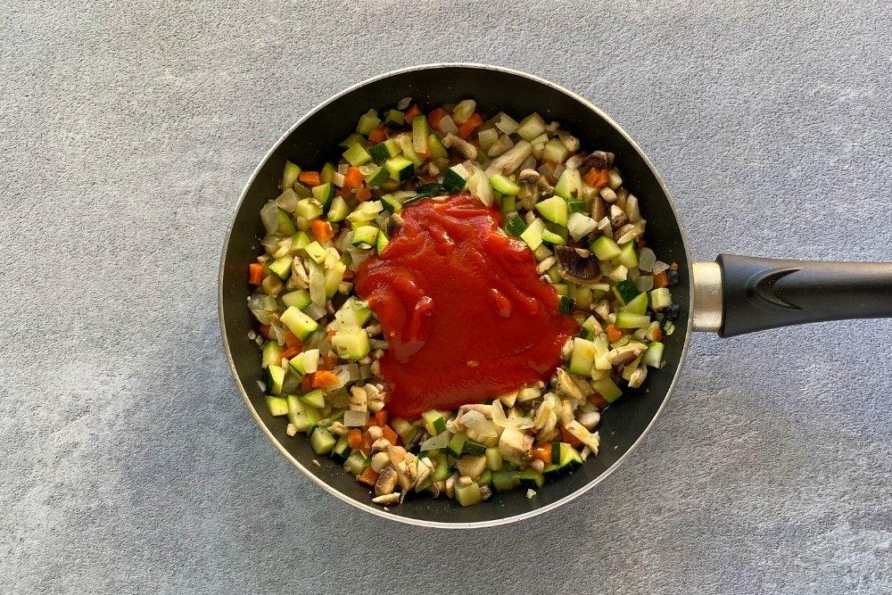 Añadir al sofrito el calabacín, los champiñones y la salsa de tomate