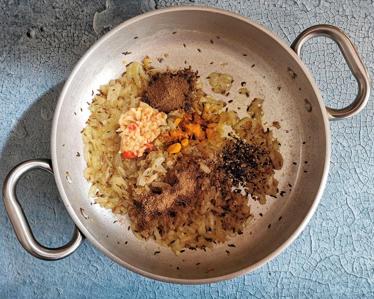 Añadir el contenido del mortero, las semillas de cilantro molidas, la pimienta molida, la cúrcuma y