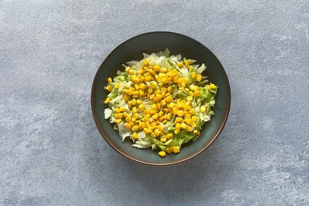 Añadir el maíz encima de la lechuga