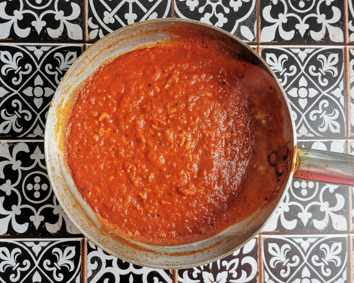 Añadir el tomate triturado y medio vaso de agua