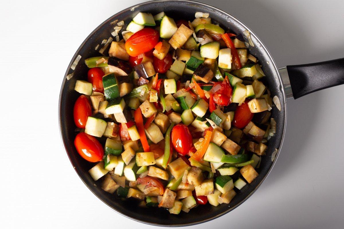 Añadir la berenjena, el calabacín y los tomates al salteado