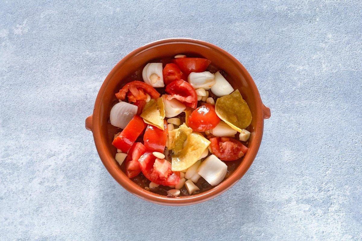 Añadir la cebolla y el tomate troceado y los ajos