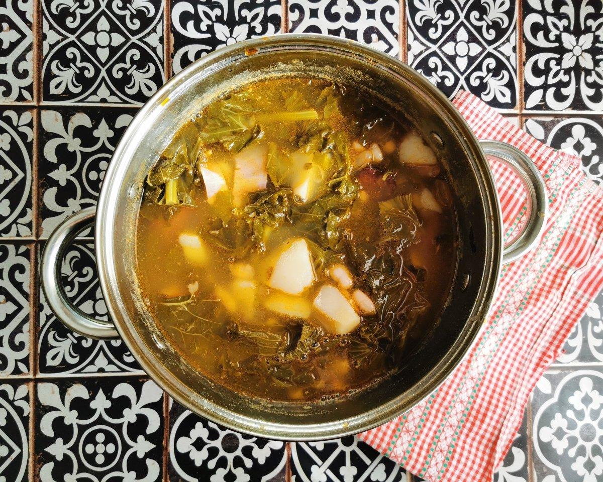 Añadir las berzas y las patatas a la olla y llevar el pote a cocción