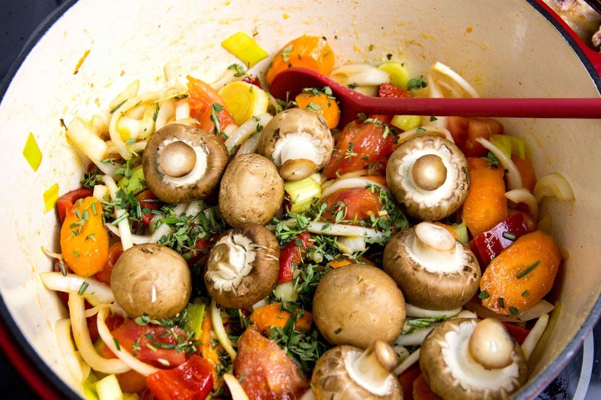 Añadir las hierbas y los champiñones a las verduras del estofado de cordero