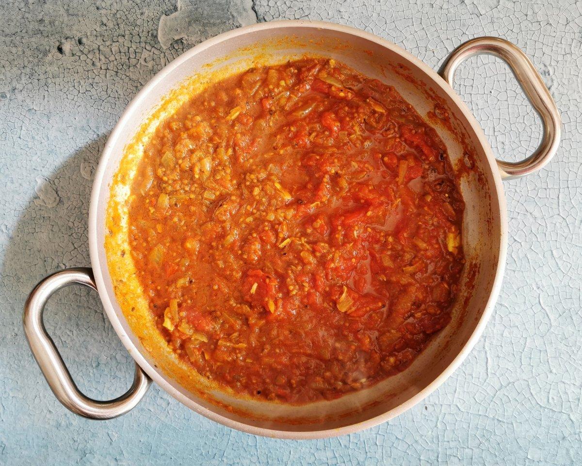 Añadir los tomates y romperlos con el tenedor.