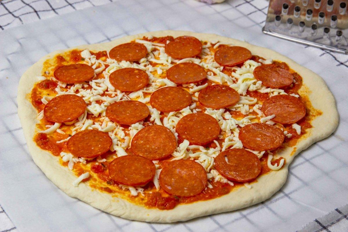 Añadir salsa de tomate y mozzarella rallada a la pizza pepperoni