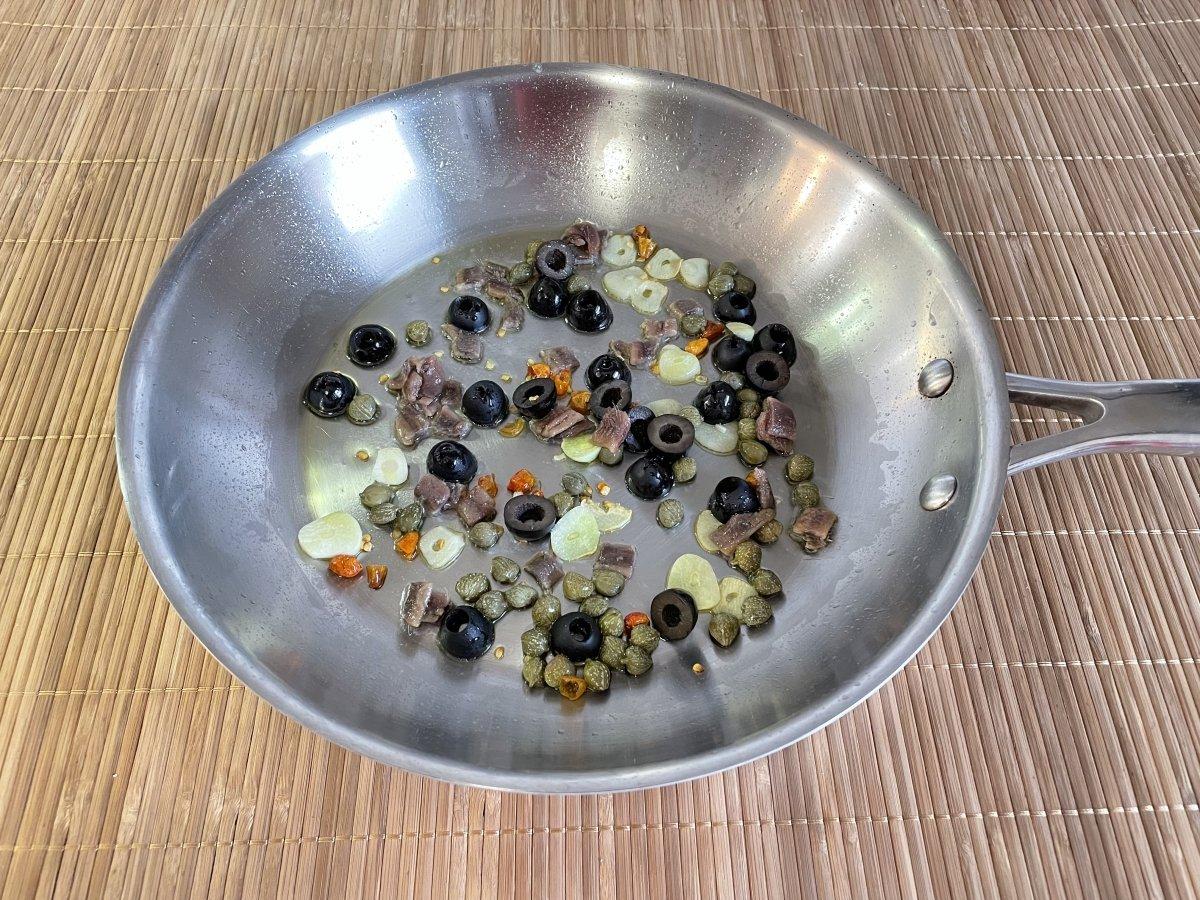 Anchoas y aceitunas añadidos a la sartén
