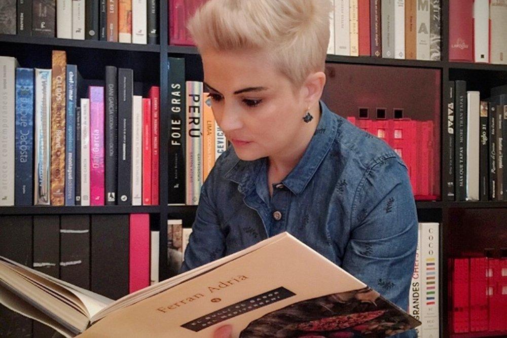 Àngels González leyendo un libro de Ferran Adrià