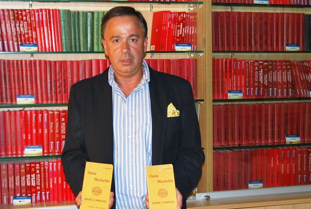 Antonio Cancela sosteniendo dos antiguas guías Michelin