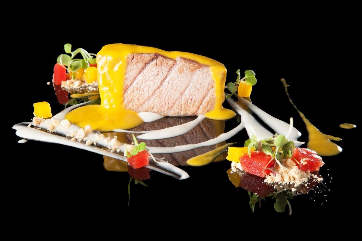 Atún rojo salvaje cocinado y bañado con salsa en un plato del restaurante El Campero