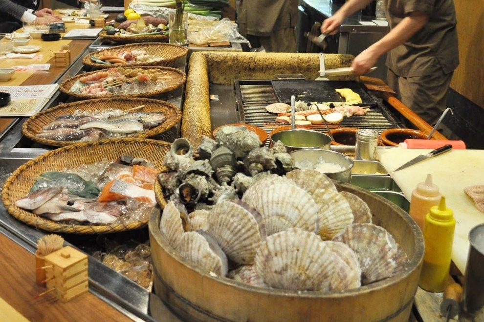 Barra de robatayaki con los alimentos alrededor