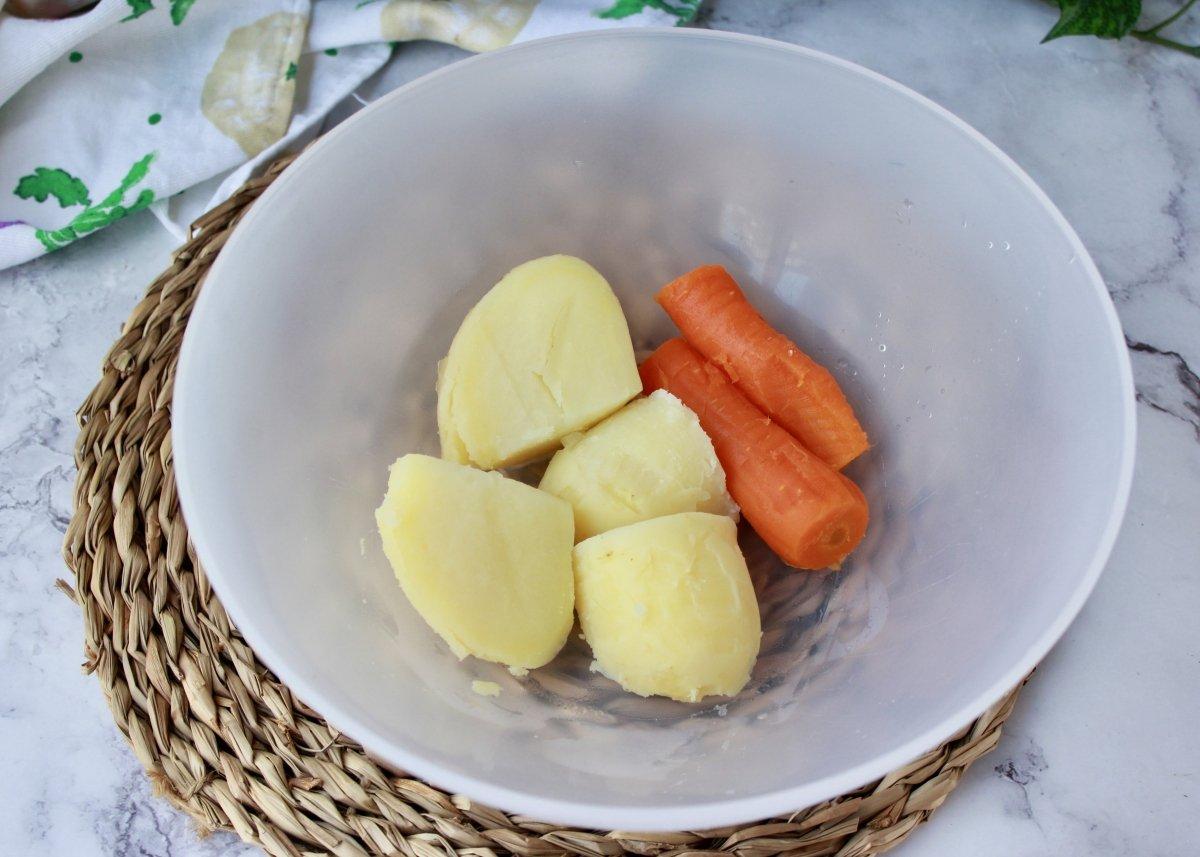 Bol con la patata y la zanahoria una vez peladas