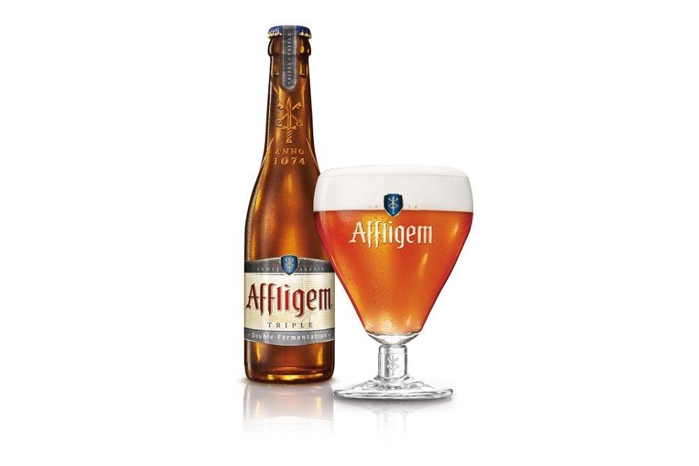 Botella de Affligem Triple junto a su copa de cáliz característica