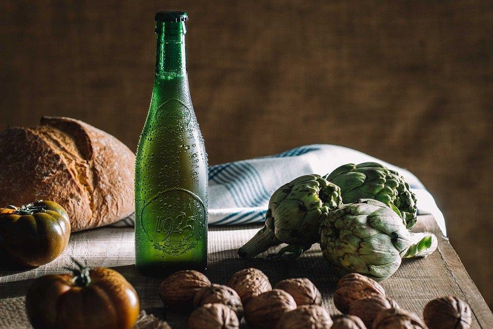 Botella de Alhambra Reserva 1925 rodeada de diferentes alimentos