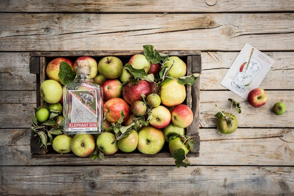 Botella de Elephant Gin sobre una caja de manzanas