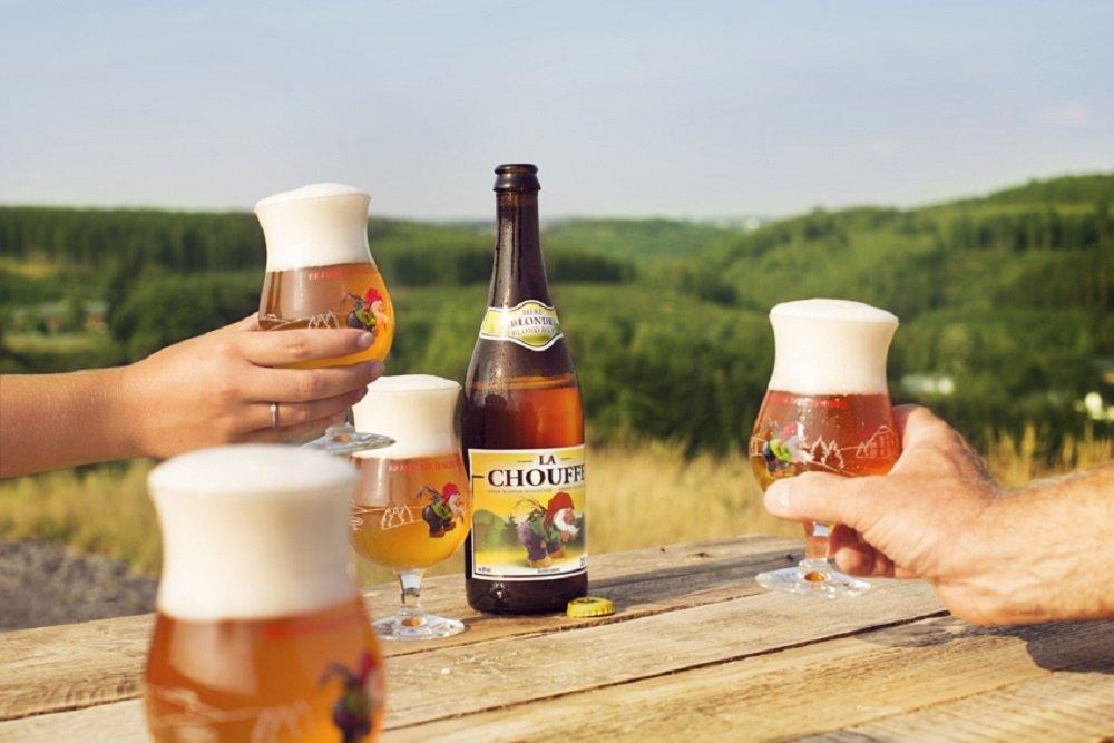 Botella de La Chouffe sobre mesa de madera y cuatro copas de cerveza