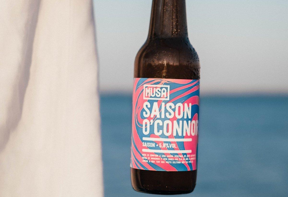 Botella de Musa Saison O'Connor frente al mar