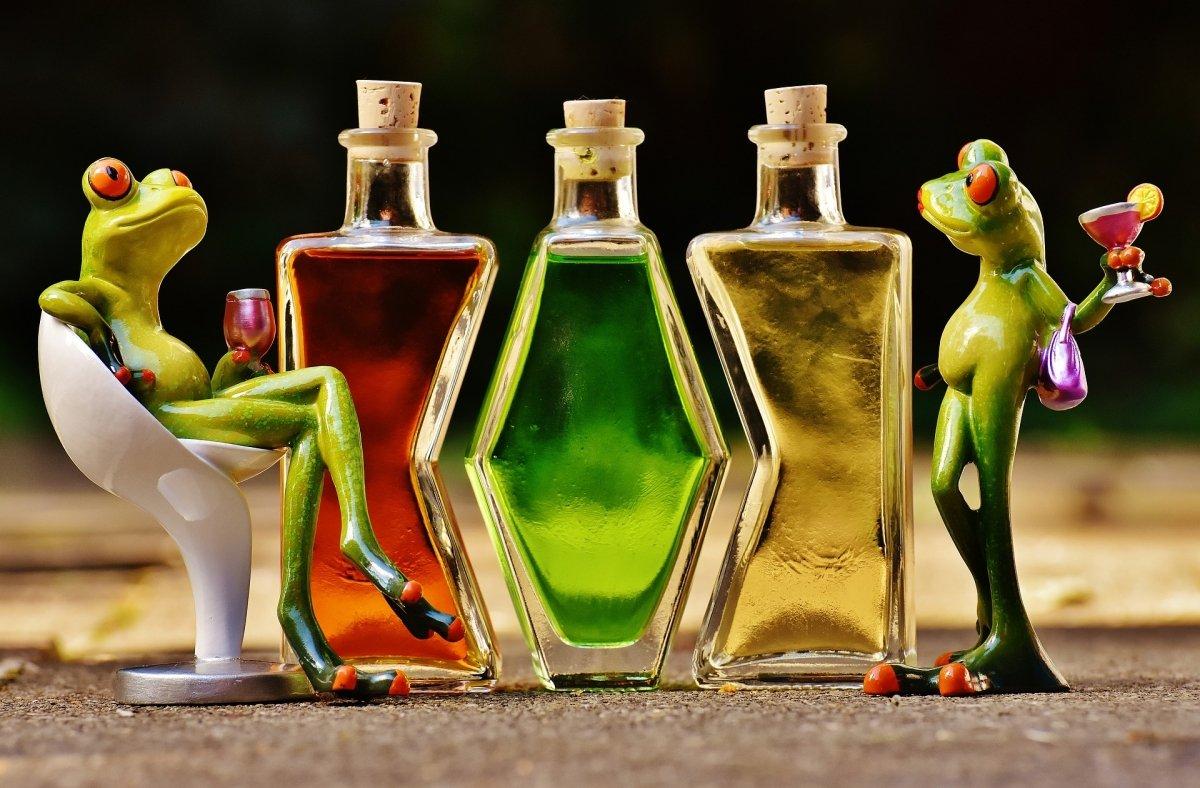 Botellas de licores de frutas junto a los muñecos de unas ranas