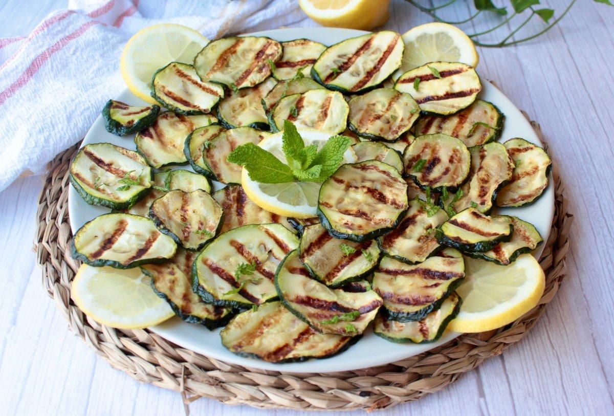 Calabacín a la plancha presentado con unas rodajas de limón y hojas de menta