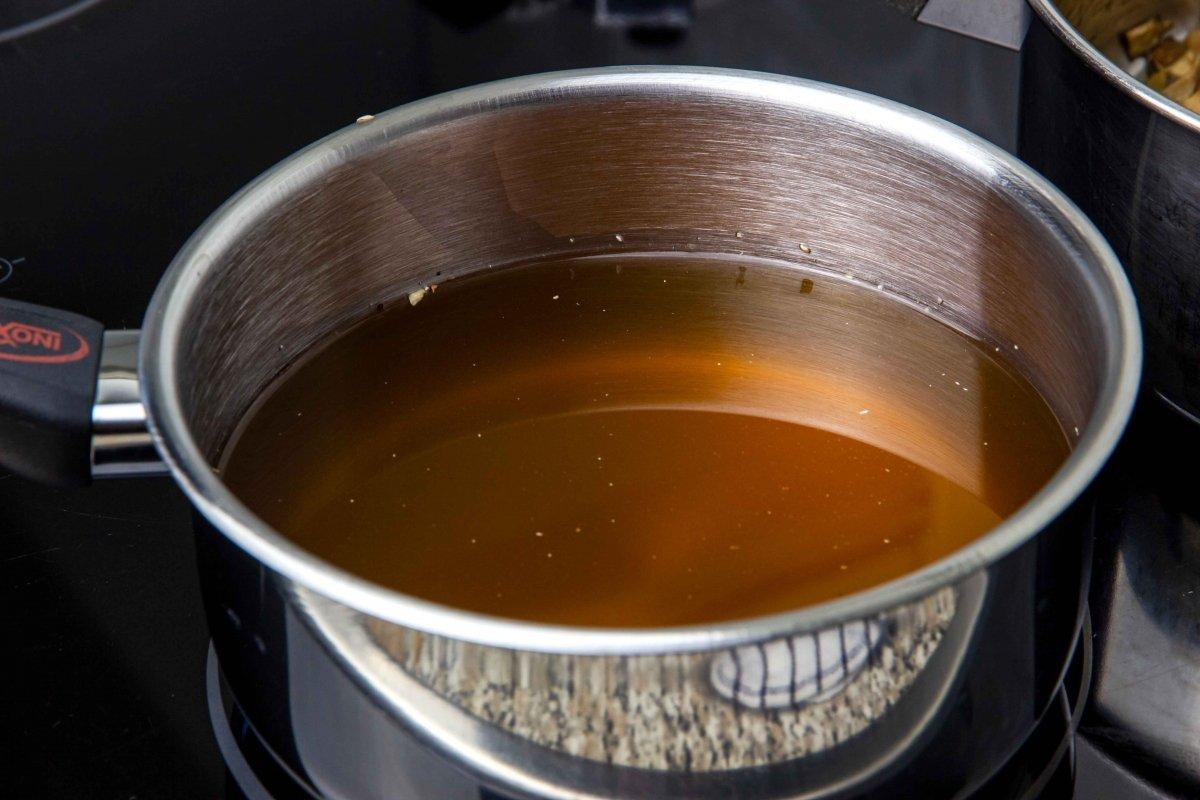 Calentar caldo para el risotto de boletus
