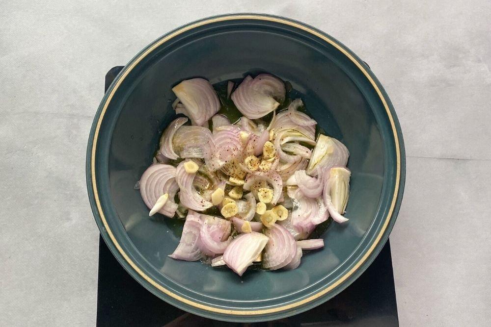 Cazuela con ajo y cebolla para la preparación de calamares en salsa americana