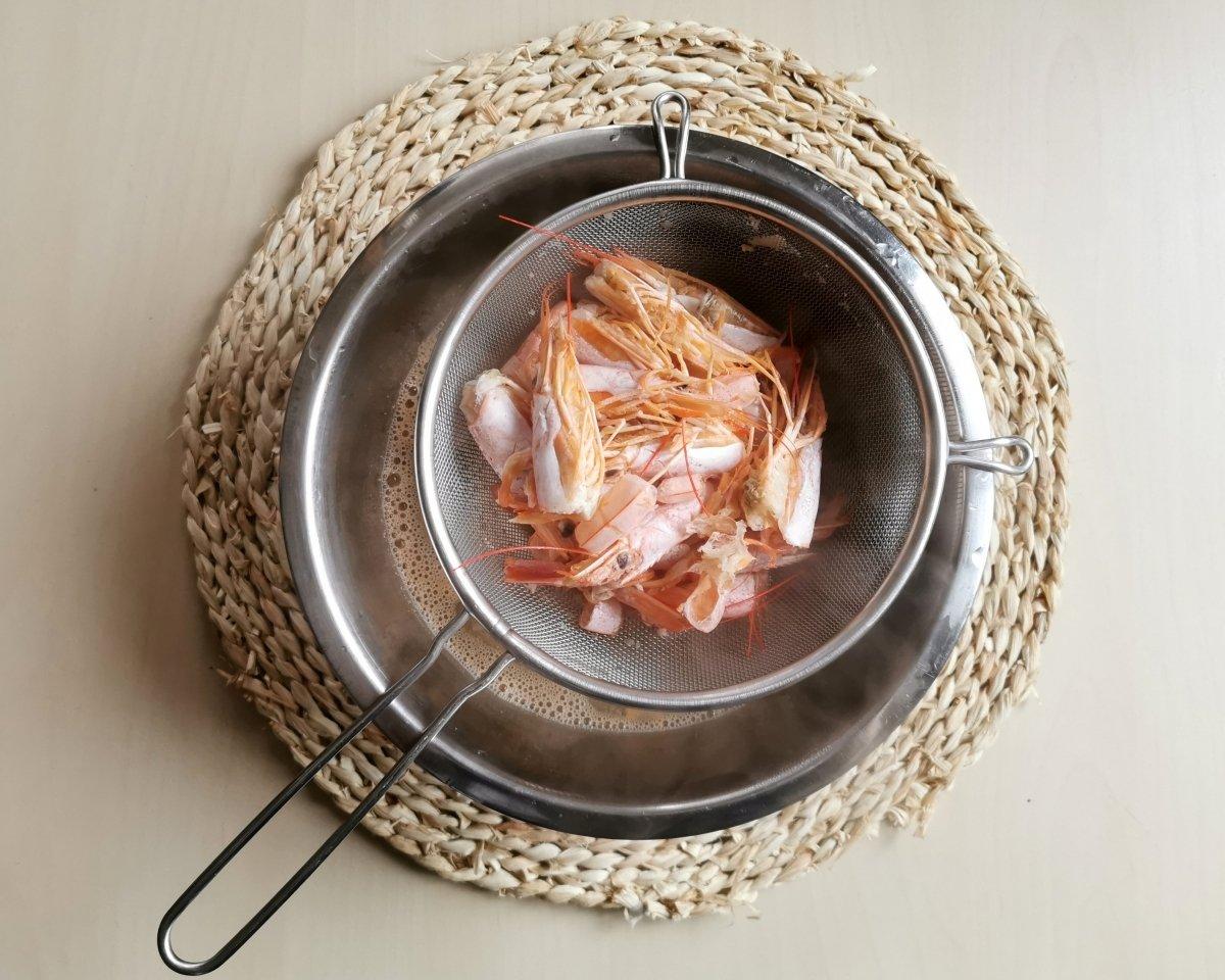 Cocer las cáscaras de los langostinos y colar el caldo