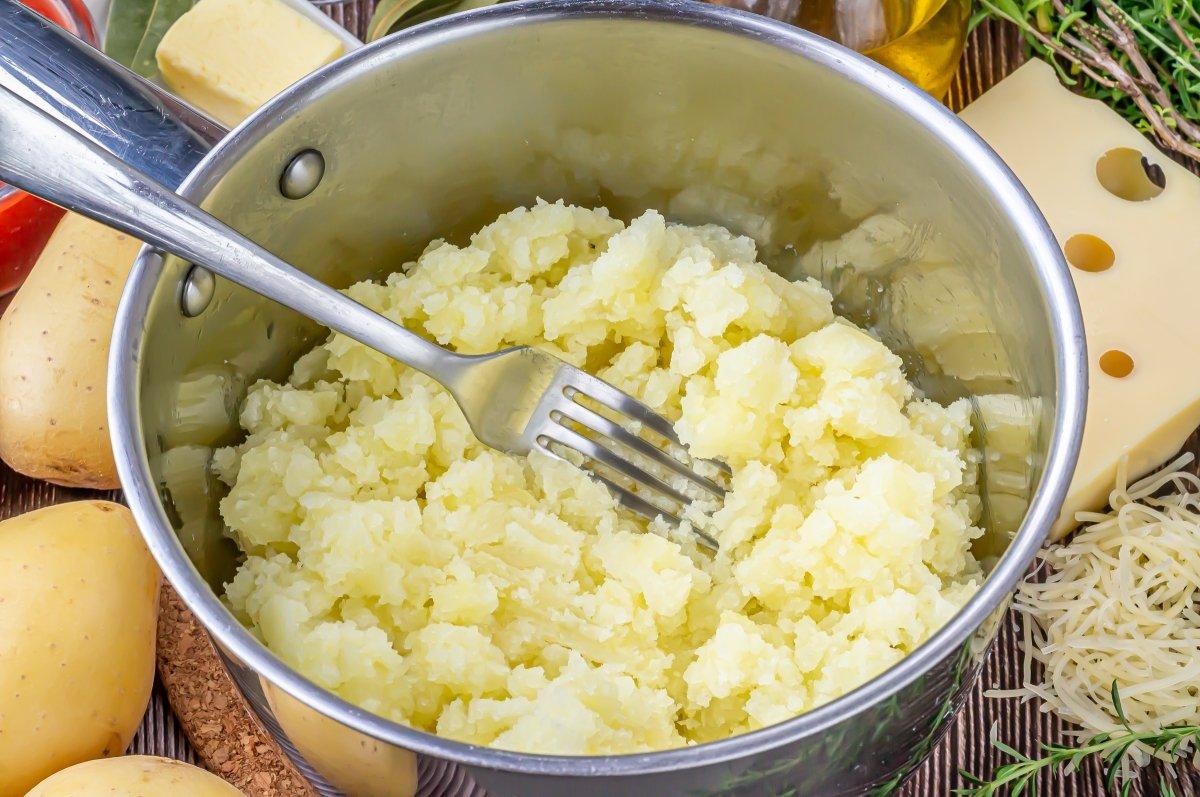 Cocer las patatas y machacarlas
