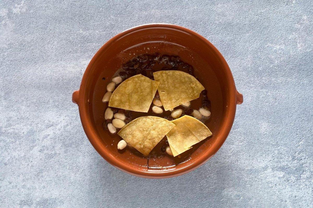 Cocinar las almendras, los cacahuetes, las pasas, el pan y la tortilla