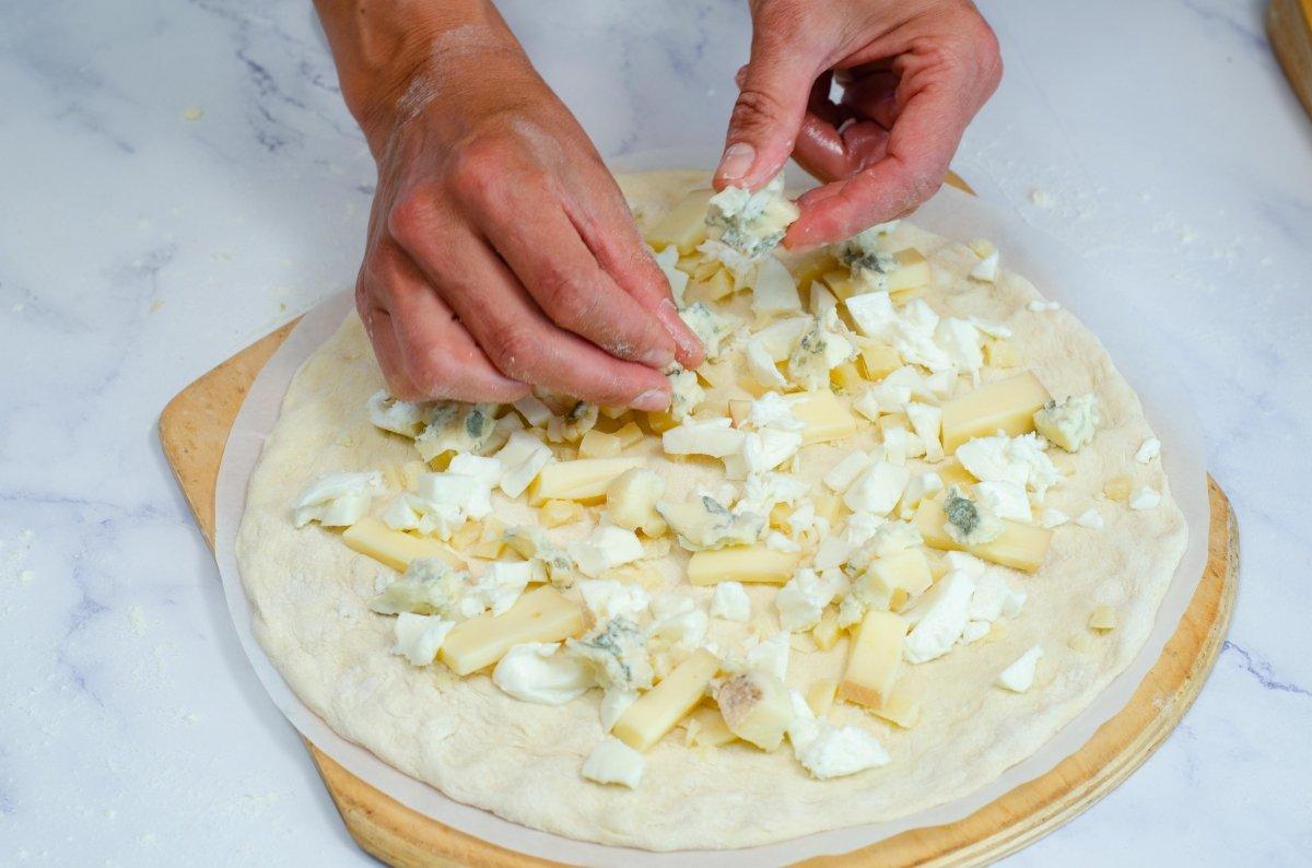 Colocando los quesos en la pizza
