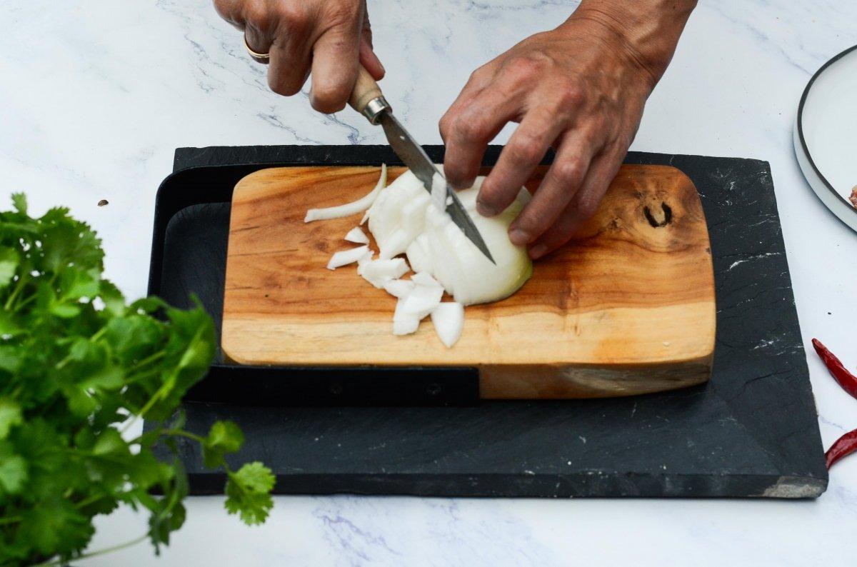 Cortando cebolla para preparar las vieiras