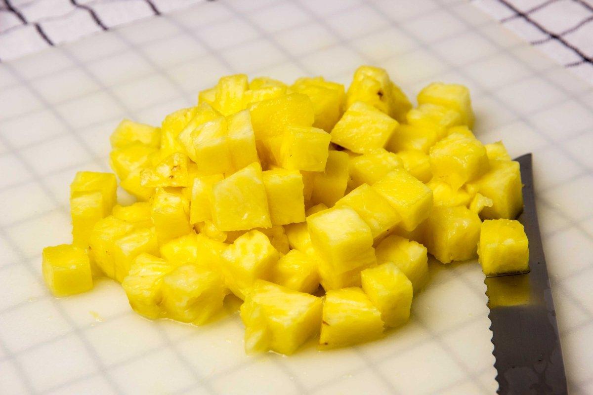 Cortar la piña en trocitos para la tarta de mango y piña