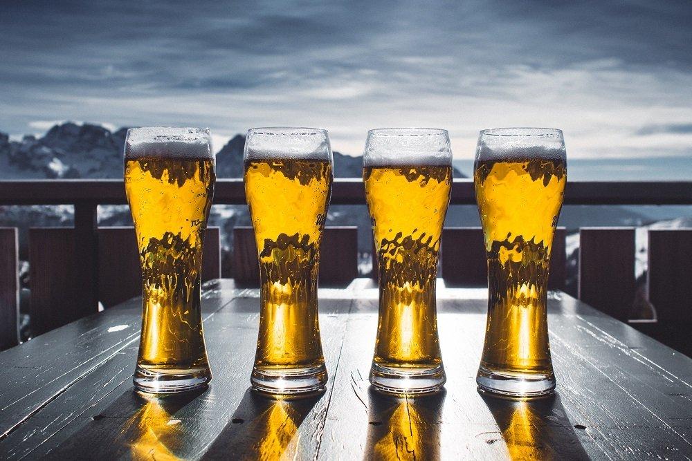 Cuatro vasos de cerveza frente a un paisaje nevado característico del País Vasco