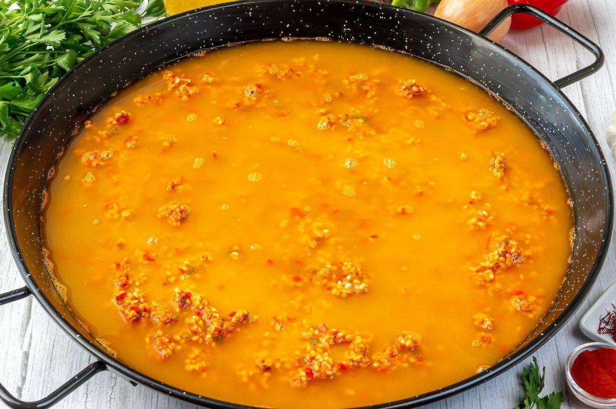 Cubrir el arroz con el caldo de marisco