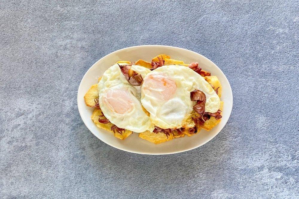Cubrir las patatas y los chipirones con los huevos fritos