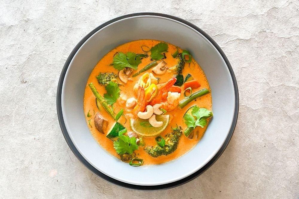 Curry rojo con langostinos acompañado de cebolleta, cilantro y anacardos