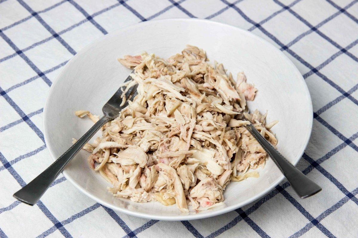 Deshebrar el pollo cocido para hacer las quesadillas de pollo