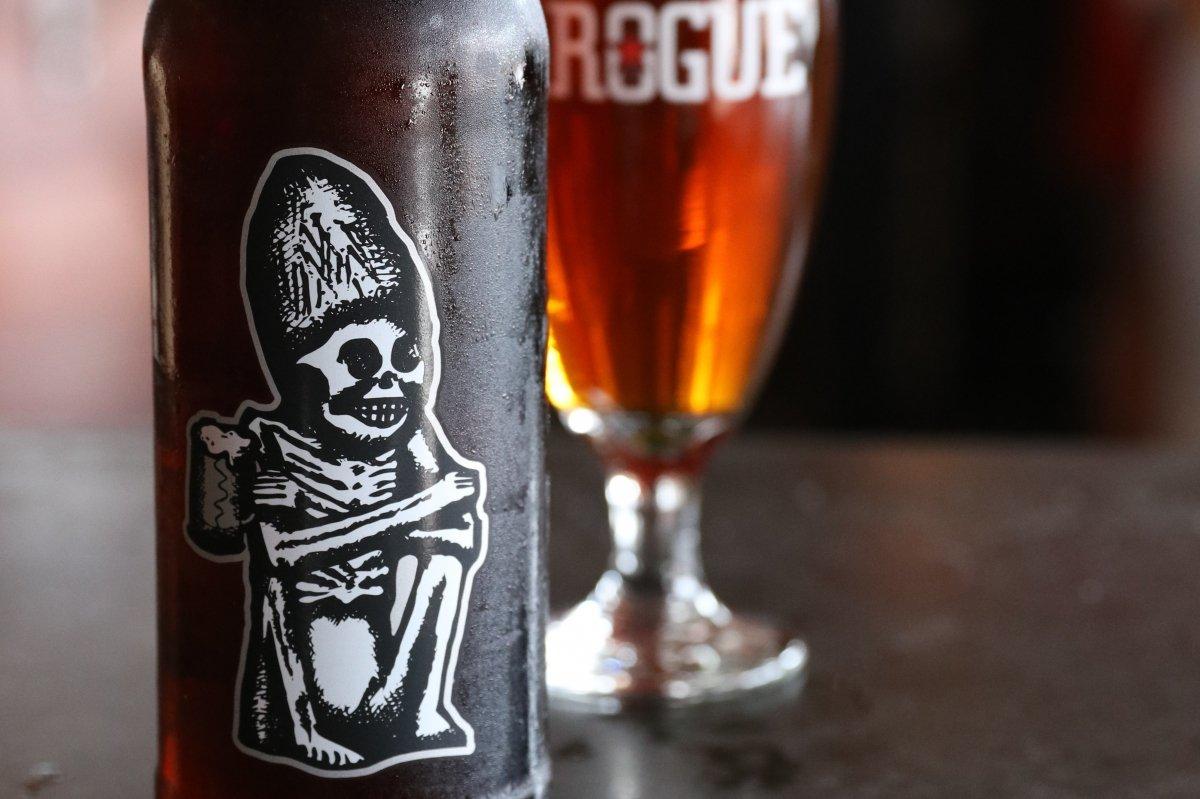 Detalle de una botella de Dead Guy Ale con copa de fondo