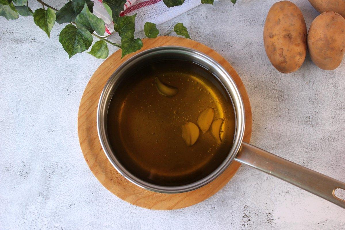 Dientes de ajo sumergidos en aceite de oliva virgen extra para ser confitados