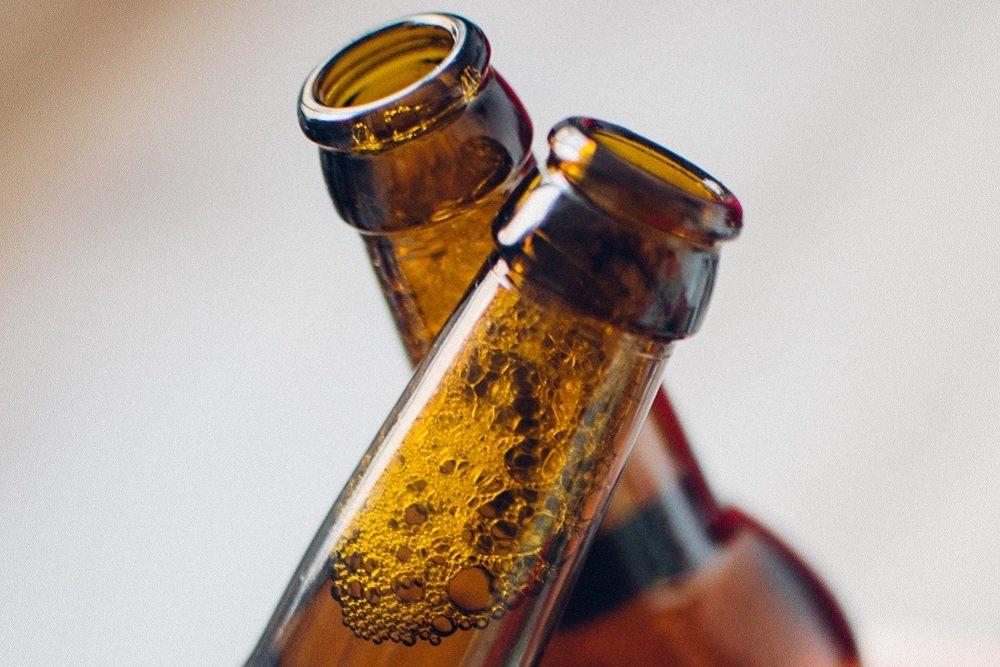 Dos botellas de cerveza chocando en forma de brindis