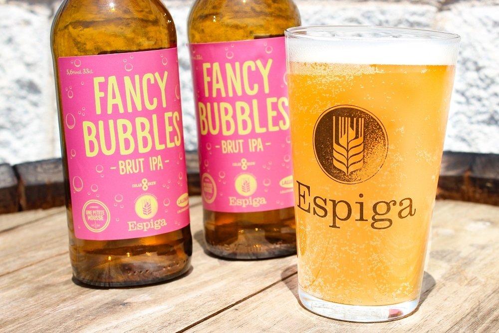 Dos botellas y un vaso de Espiga Fancy Bubbles sobre un barril de madera