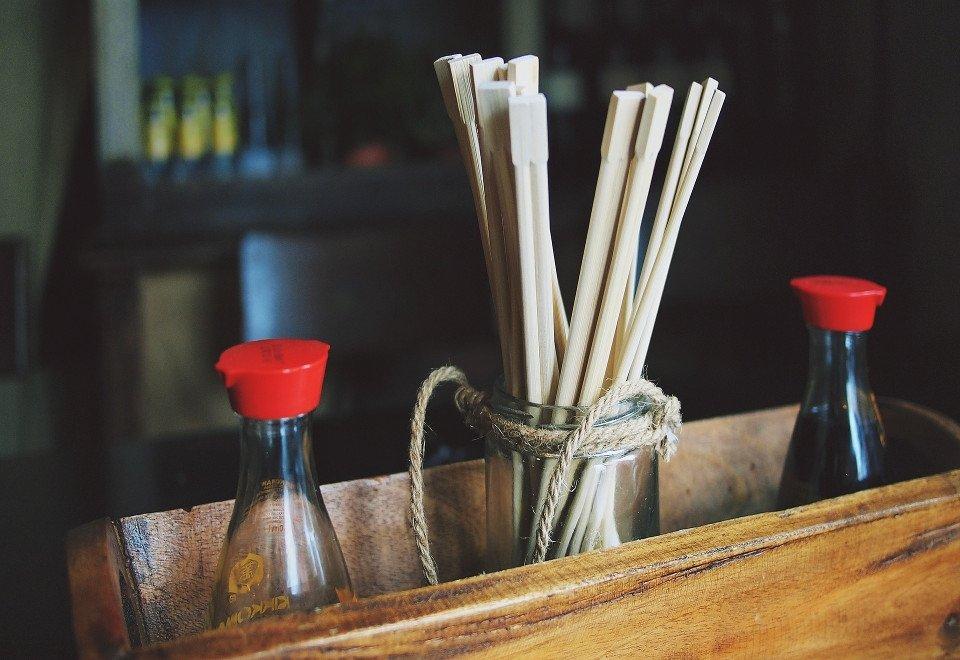 Dos botes de soja con palillos en un restaurante