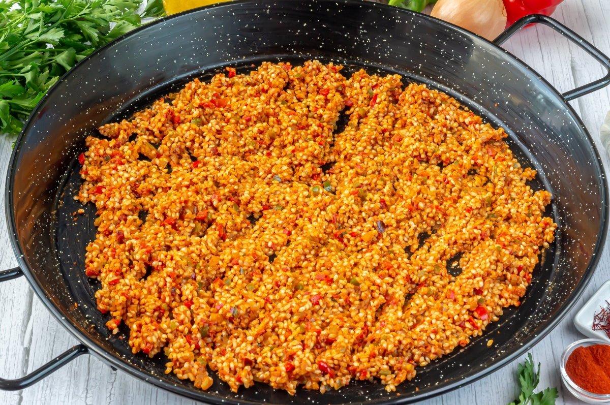 Echar el arroz en la paellera