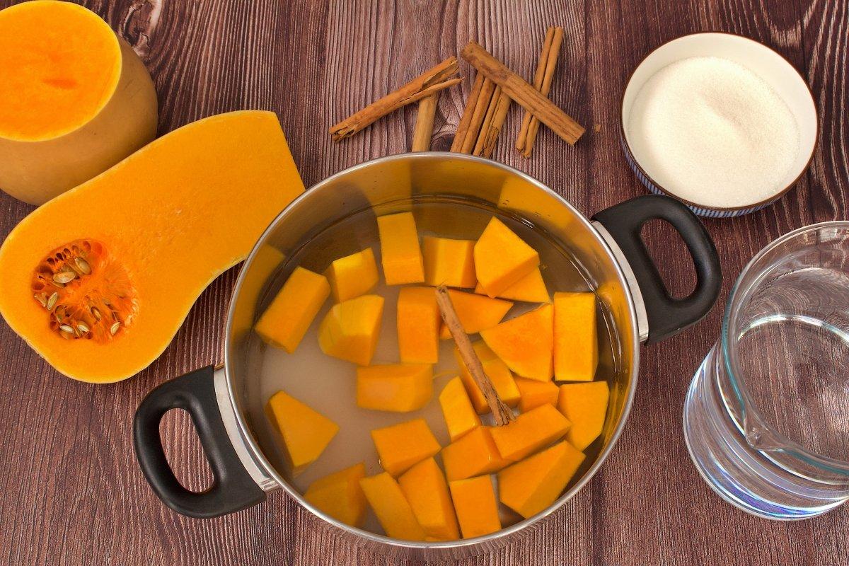 El azúcar y una rama de canela añadidas en la olla de la mermelada de calabaza